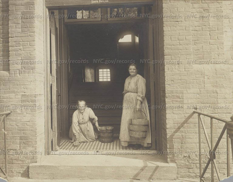 City Home, Two old women with wooden pails scrub entry to South Pavilion.