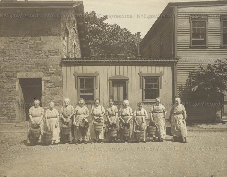 City Home: Ten old women holding buckets, standing in front of 1-story wooden house wedged between 2-story houses.