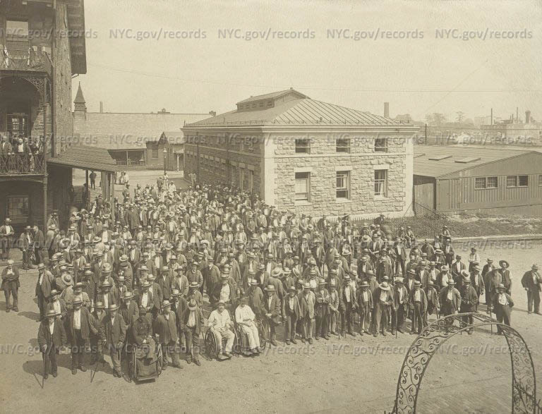 City Home: Large group of old men crowded in grounds, as if waiting to enter through gate in foreground.