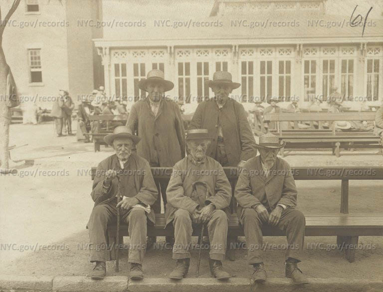 City Home District: Three old men seated on outdoor bench; 2 old men stand behind them. All wear straw hats.