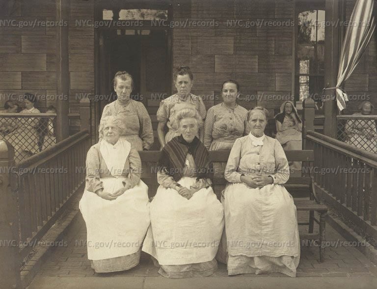City Home District: Three old women seated on bench, three others standing behind them on porch.