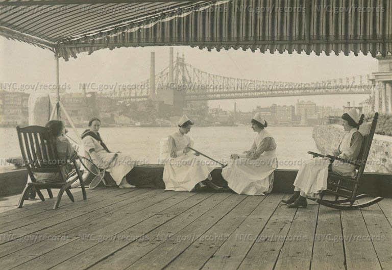 Training School Nurses on deck of Training School: 2 with tennis racquets, 2 others seated on ledge, a 5th in rocking chair.
