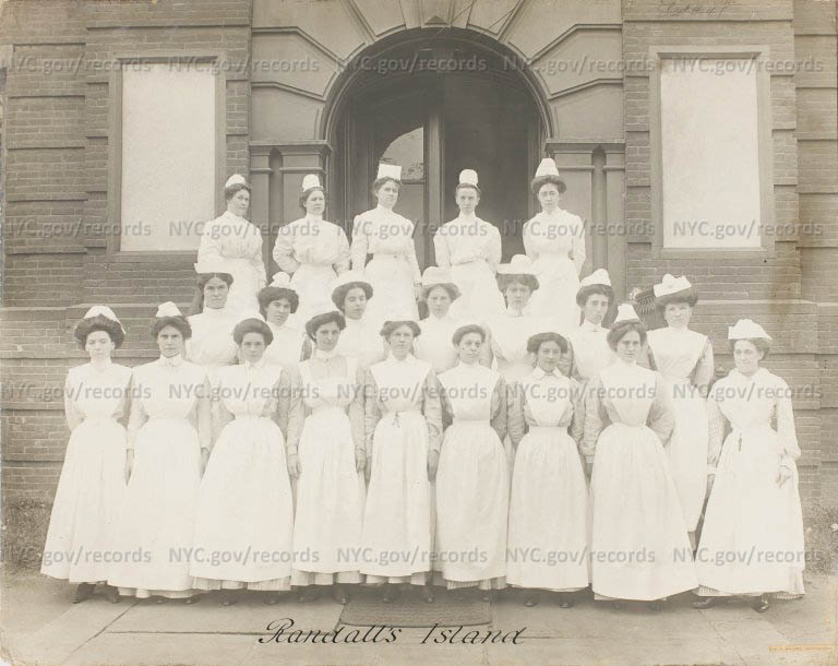 Randall's Island (Nurses) : Three rows of nurse in white uniforms stand on stairs in front of building.