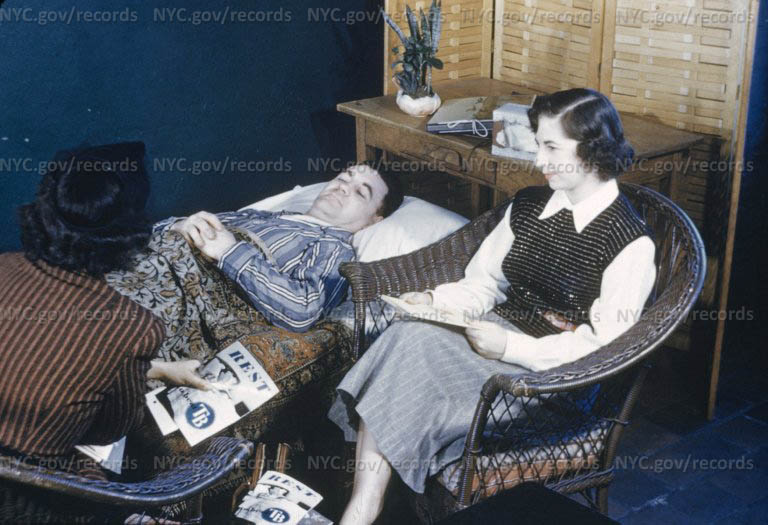 Patient lies on couch as woman takes case history. Pamphlets on TB scattered on chair.