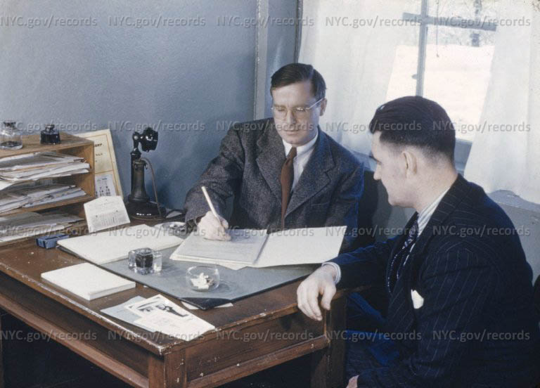 Physician at desk explaining records to patient.
