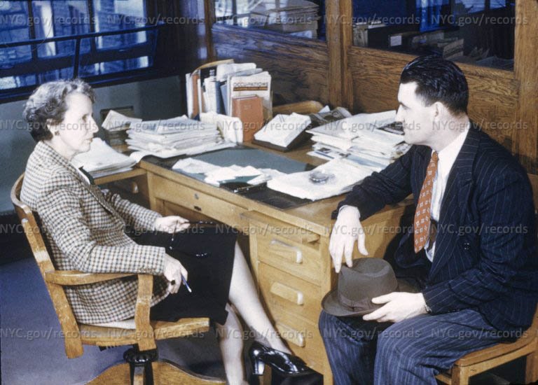 Woman at desk; patient seated alongside. (Patient being dismissed from hospital?)