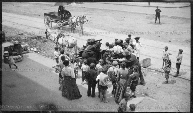 Crowd of children and adults gathered around horse drawn roundabout ride.