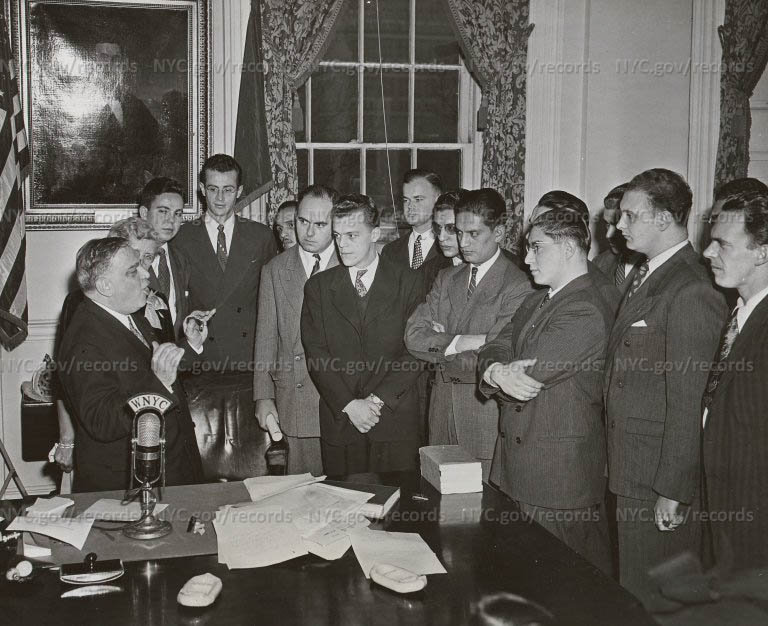 """""""Latin American students honor LaGuardia"""" as a group stands around his desk, listening to the Mayor speak to them."""