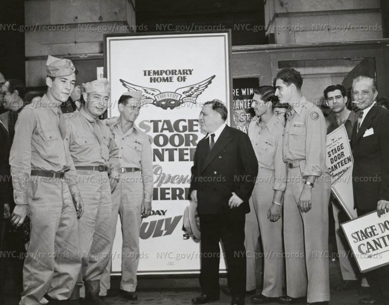 LaGuardia with soldiers standing in front of sign announcing Temporary Home of Stage Door Canteen Opening Here...