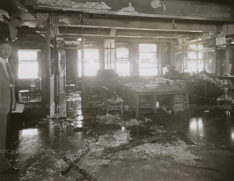 Empire State Building Disaster: Interior, S corner, 79th Fl. Offices; charred bodies on desk in background.; 11:50 am.
