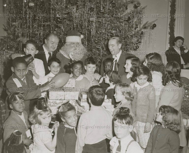 Santa Claus, wrapped presents, children looking at Santa Claus, mayor laughing. Tree in background. (City Hall Christmas Party.)