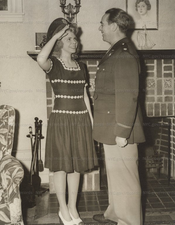 Niece Joan, wearing Major's cap, saluted O'Dwyer (in uniform) in front of family fireplace.