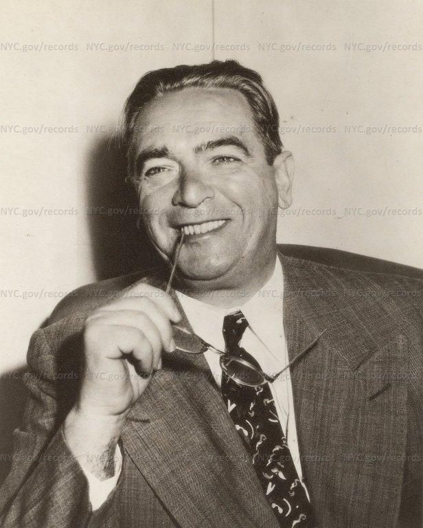 Portrait of William O'Dwyer: Mayor smiling, holding eyeglasses.