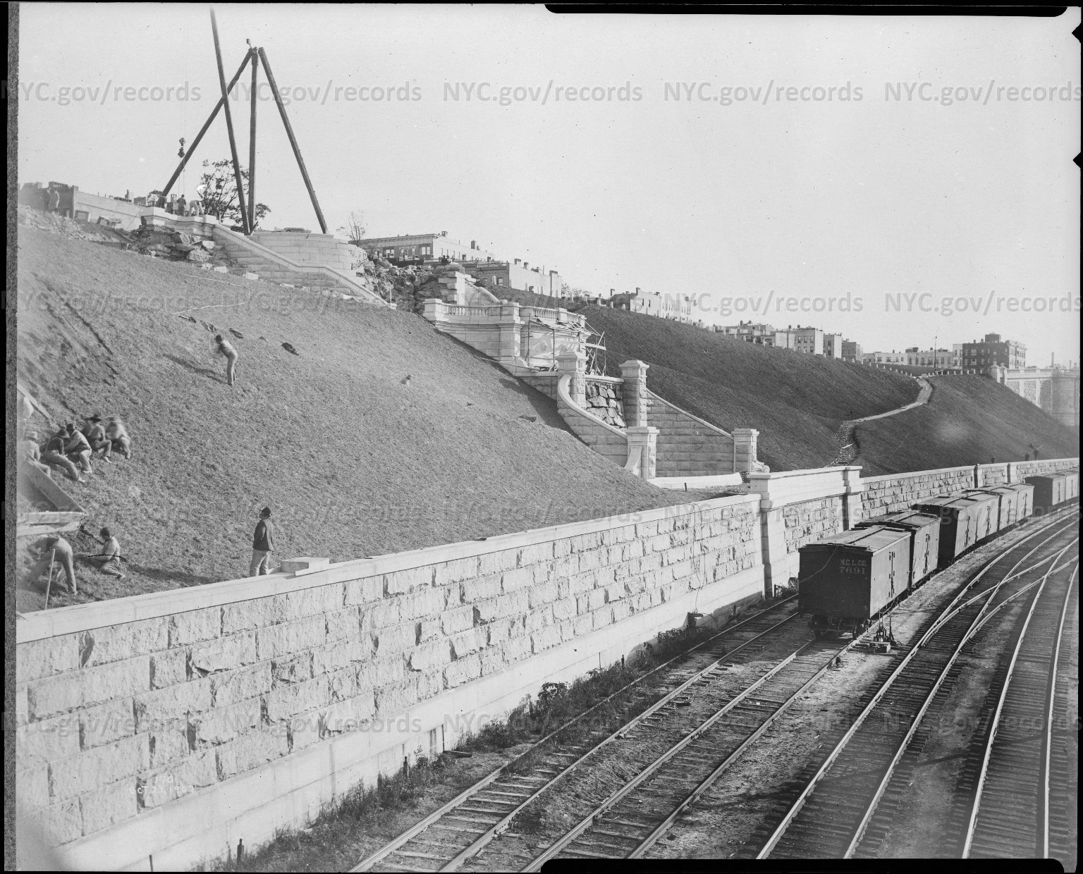 Constructing terrace, freight train; houses in background